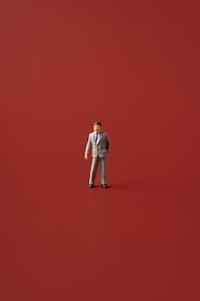 Homem de negócios em miniatura em uma parede vermelha isolada