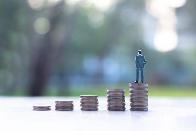 Homem de negócios em miniatura na pilha de moedas