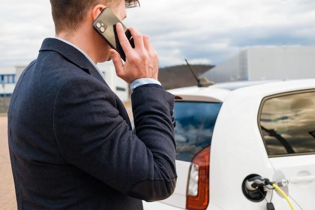Homem de negócios em pé perto do carregador elétrico e falando no smartphone