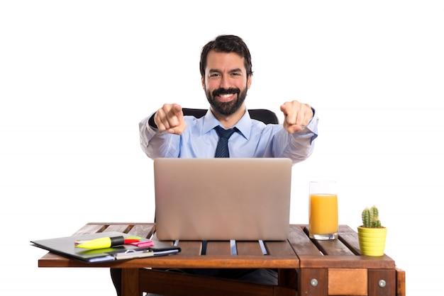 Homem de negócios em seu escritório apontando para a frente