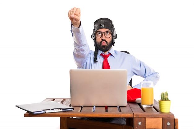 Homem de negócios em seu escritório com chapéu piloto