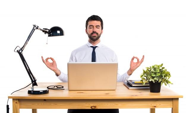 Homem de negócios em seu escritório em posição zen
