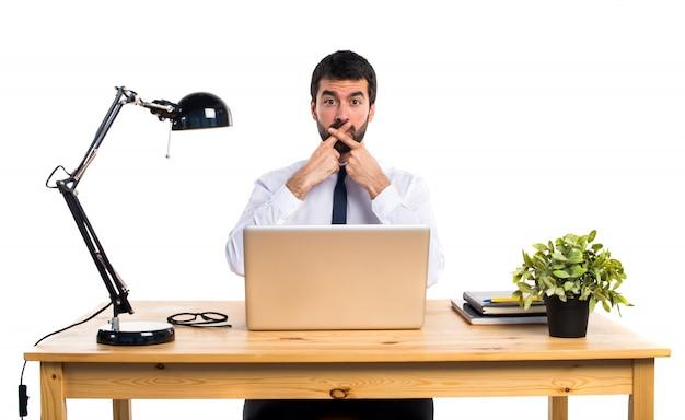 Homem de negócios em seu escritório fazendo um gesto de silêncio