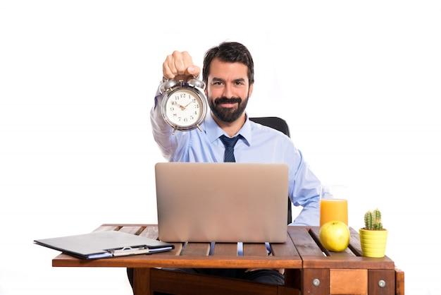 Homem de negócios em seu escritório segurando um relógio