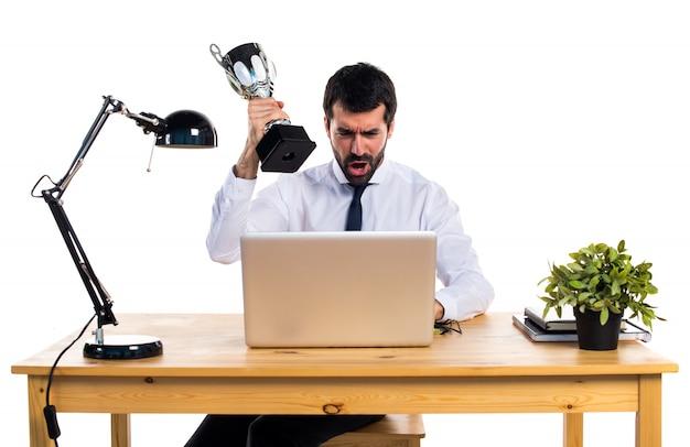 Homem de negócios em seu escritório segurando um troféu