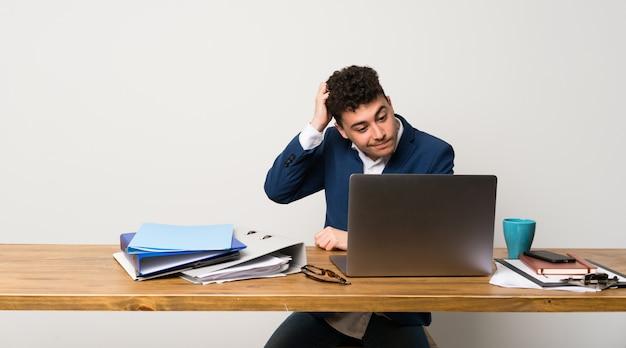 Homem de negócios em um escritório com dúvidas enquanto coçando a cabeça