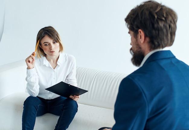 Homem de negócios em um terno clássico e uma mulher no sofá com documentos nas mãos de um psicólogo trabalhando.