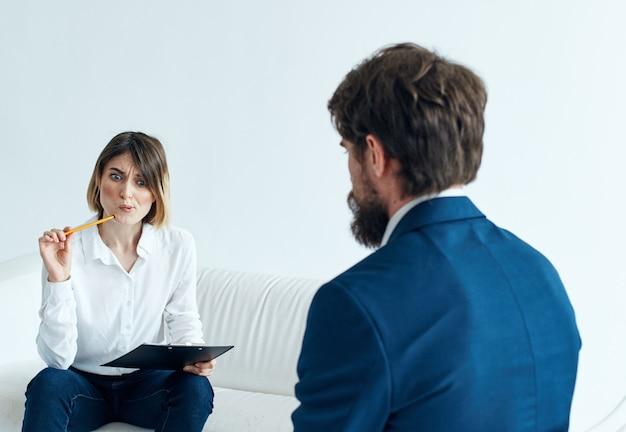 Homem de negócios em um terno clássico e uma mulher no sofá com documentos nas mãos de um psicólogo.