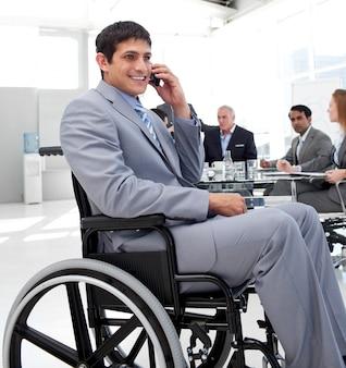 Homem de negócios em uma cadeira de rodas no telefone durante uma reunião