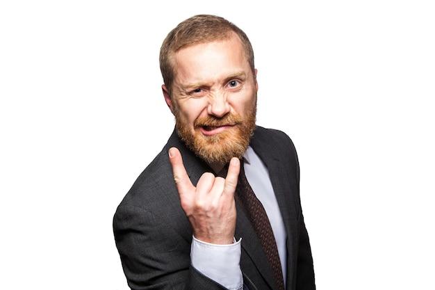 Homem de negócios engraçado fazendo gesto de chifre - sinal de rock and roll. isolado no fundo branco, olhando para a câmera.