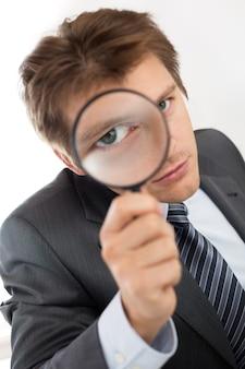 Homem de negócios engraçados segurando o retrato da lupa. investigação de detetive particular, camada, crime, pesquisa de negócios ou conceito de segurança