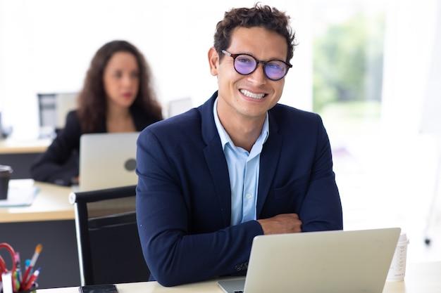 Homem de negócios entrepreneu olhar para a câmera e trabalhar no colega de computador portátil em plano de fundo no escritório em casa.