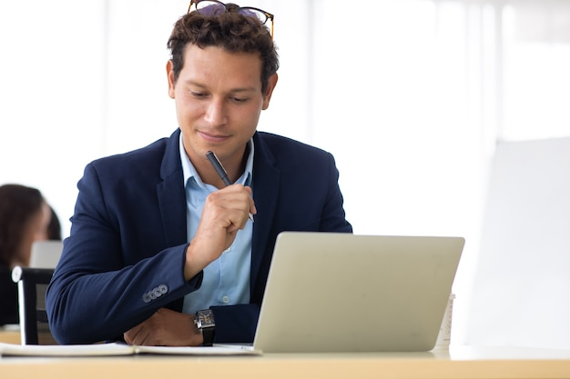 Homem de negócios entrepreneu trabalhando no colega de computador portátil no fundo no escritório em casa.
