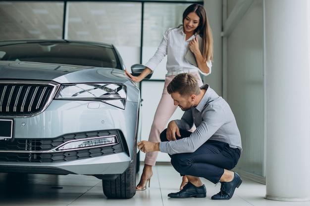 Homem de negócios escolhendo um carro com uma vendedora no salão de automóveis