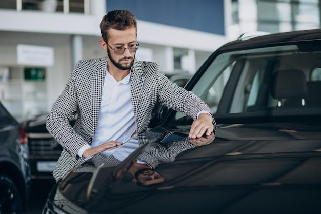 Homem de negócios escolhendo um carro em um showroom de carros
