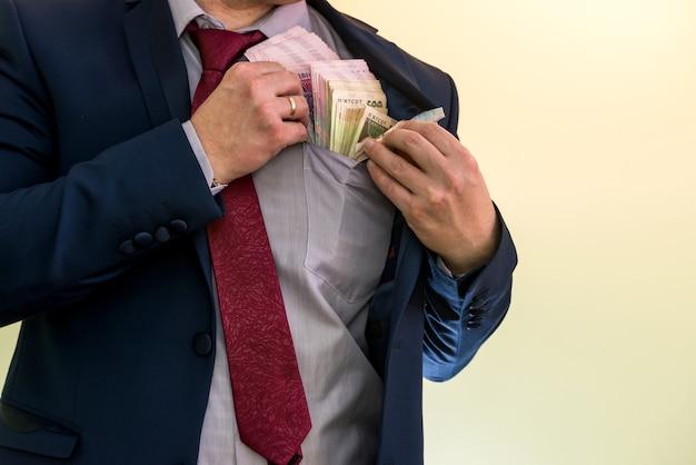Homem de negócios escondendo matilha da ucrânia no bolso do terno