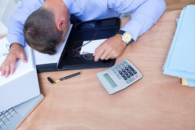 Homem de negócios esgotado dormindo na mesa