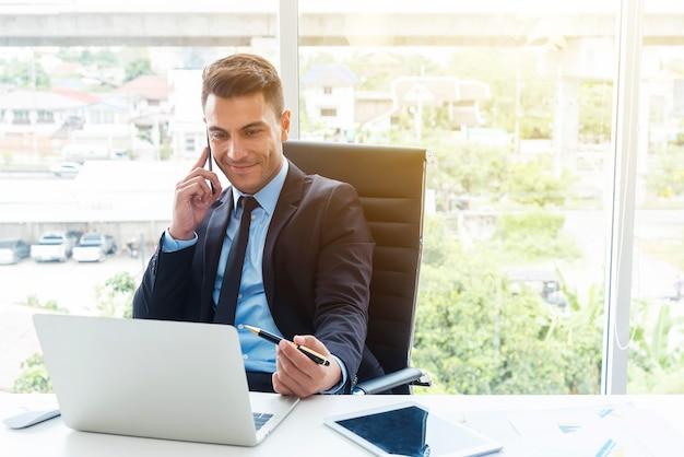Homem de negócios esperto que usa o móbil e o portátil no escritório.
