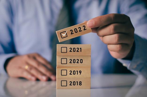 Homem de negócios está escolhendo a opção 2022 para celebrar o ano novo que se aproxima com blocos de madeira