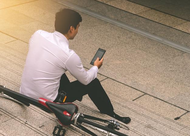 Homem de negócios está relaxando ouvindo música com sua bicicleta ao lado