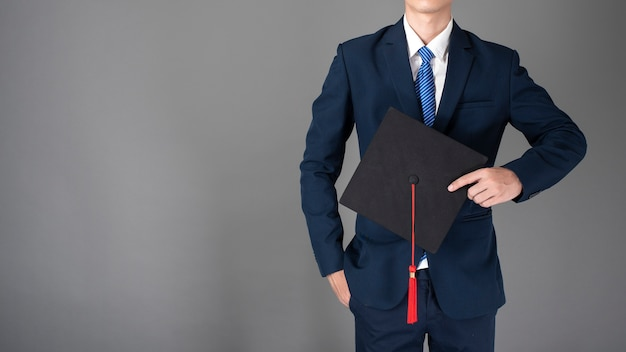 Homem de negócios está segurando o chapéu de formatura, conceito de educação de negócios