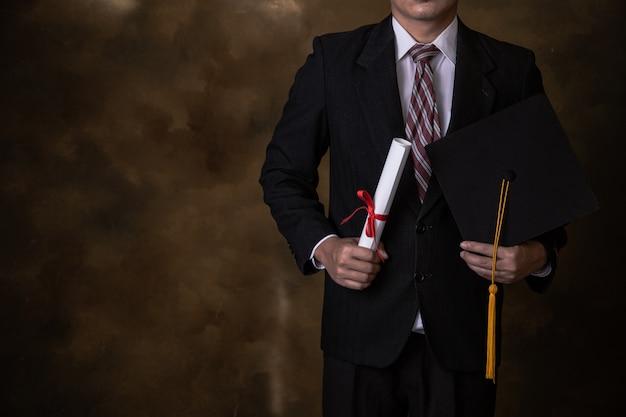 Homem de negócios está segurando o chapéu de formatura