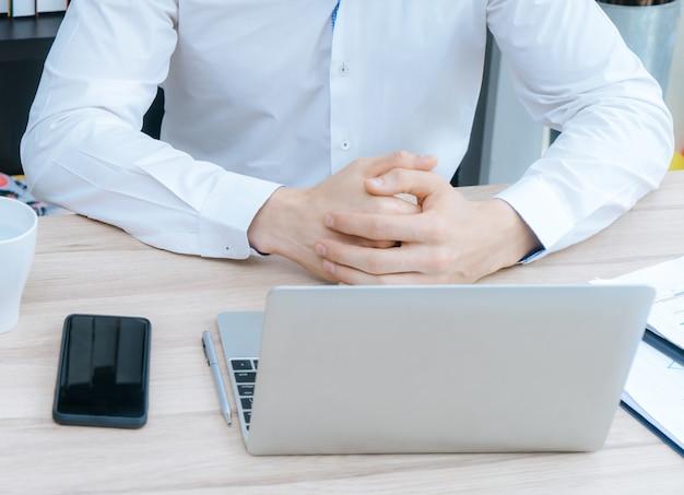 Homem de negócios está trabalhando no computador na mesa pelas janelas