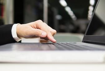 Homem de negócios está usando o computador portátil em seu escritório