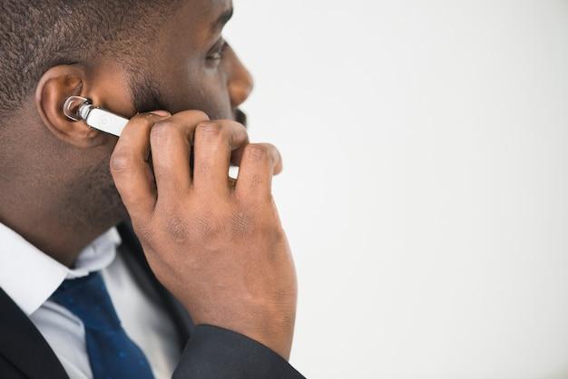 Homem de negócios étnico que ajusta o fone de ouvido