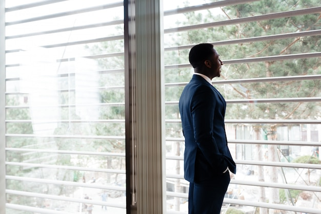 Homem de negócios executivo americano africano alegre bonito no escritório do espaço de trabalho