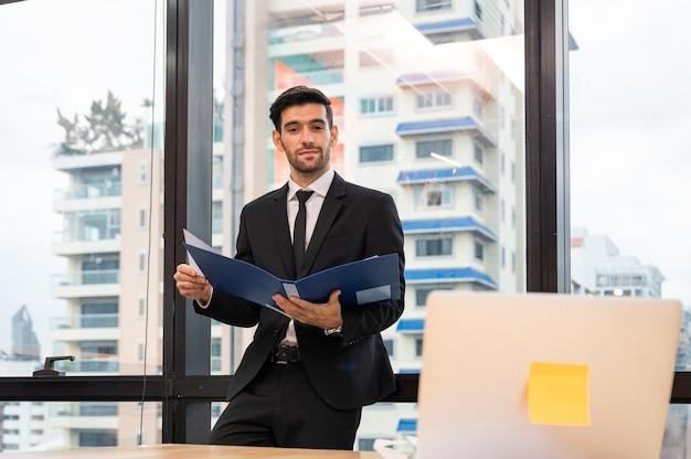 Homem de negócios executivo inteligente caucasiano em pé segurando uma pasta de documentos, olhando para o laptop no escritório