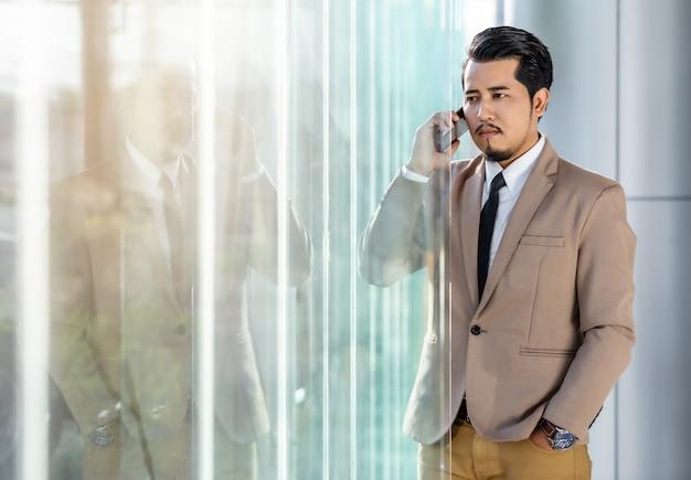 Homem de negócios, falando com o celular no escritório