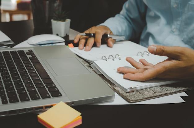 Homem de negócios faz anotações em um planejador de estratégia de marketing e estatísticas, analisa os dados do computador.