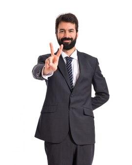 Homem de negócios fazendo o gesto da vitória sobre fundo branco
