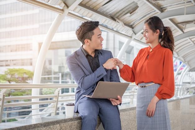 Homem de negócios feliz apresentando apertando as mãos com a empresária para parceiros de negócios