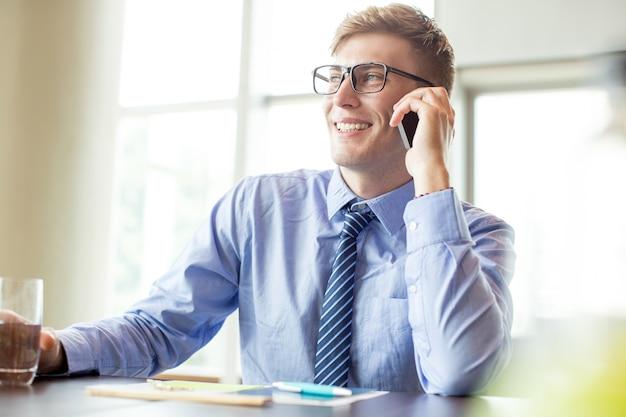 Homem de negócios feliz chamando o telefone na mesa do escritório