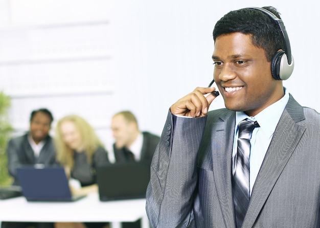 Homem de negócios feliz com pessoas ao fundo