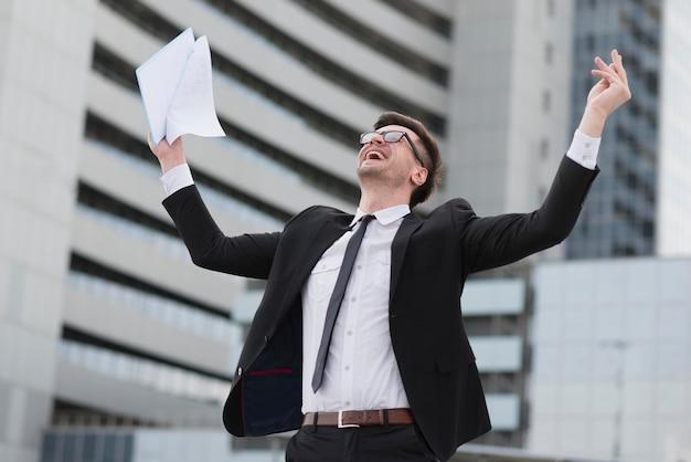 Homem de negócios feliz de baixo ângulo