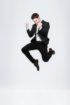 Homem de negócios feliz de corpo inteiro em terno preto pulando e comemorando o sucesso isolado em uma parede branca