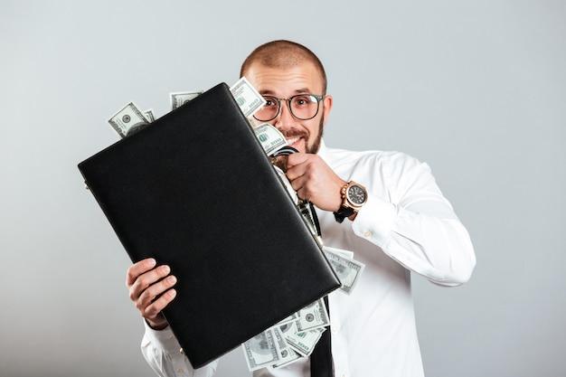 Homem de negócios feliz de óculos e camisa segurando o diplomata cheio de dinheiro, isolado sobre a parede cinza