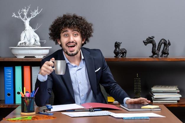 Homem de negócios feliz de vista frontal com roupa formal, sentado à secretária no escritório