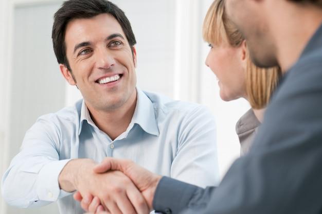 Homem de negócios feliz e sorridente apertando as mãos após uma transação no escritório