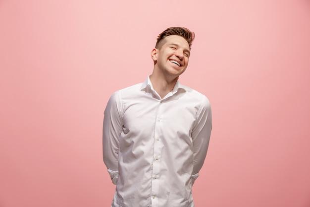 Homem de negócios feliz em pé e sorrindo contra fundo rosa.