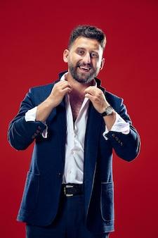 Homem de negócios feliz em pé e sorrindo isolado na parede vermelha do estúdio