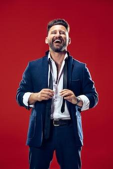 Homem de negócios feliz em pé e sorrindo isolado no estúdio vermelho