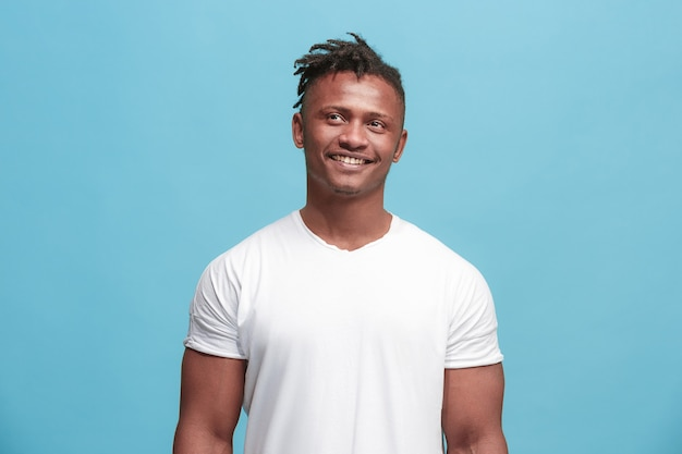 Homem de negócios feliz em pé e sorrindo, isolado no fundo azul do estúdio. retrato de metade do corpo masculino afro-americano. jovem emocional. as emoções humanas, o conceito de expressão facial. vista frontal.