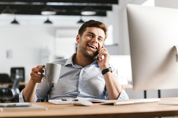 Homem de negócios feliz falando pelo smartphone e bebendo café enquanto está sentado à mesa no escritório