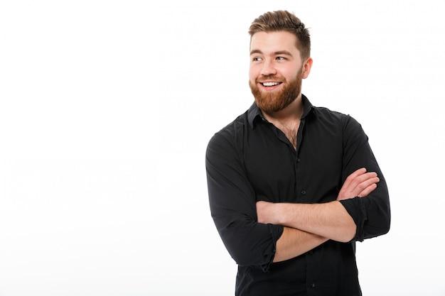 Homem de negócios feliz na camisa com os braços cruzados, olhando para longe