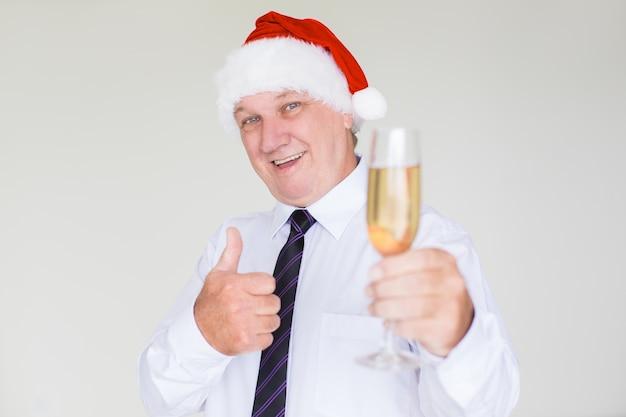 Homem de negócios feliz no chapéu do papai noel com champanhe
