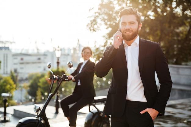 Homem de negócios feliz posando ao ar livre, falando por telefone